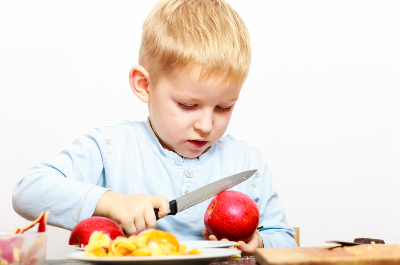 boy with sharp knife cutting apples