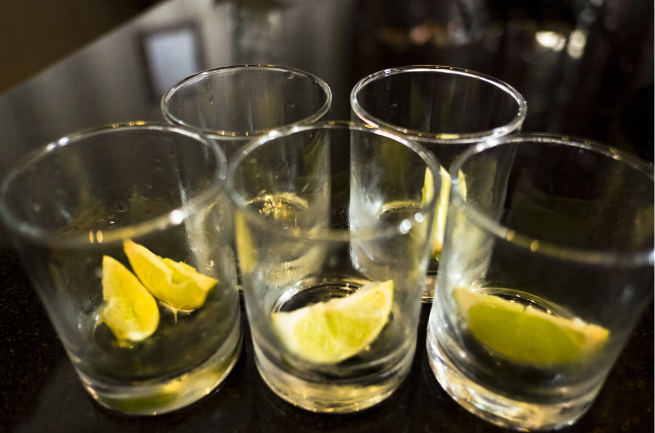 Empty shot glasses with lime wedges